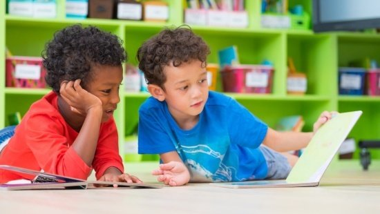 Dois meninos, um de camiseta vermelha e outro de camiseta azul, estão deitados no chão da sala de aula. O de camiseta azul folheia um livro enquanto o de camiseta vermelha apoia a cabeça na mão.