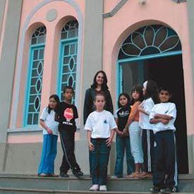 Ana Flávia e os alunos em frente à igreja construída em 1937: no passado, as mulheres só podiam ir à missa com véu na cabeça. Foto: Marie Ange Bordas
