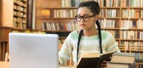Adolescente faz pesquisa em livros e no computador