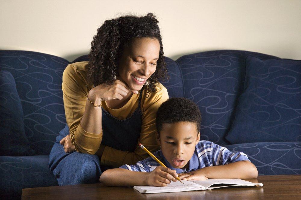 Sala de uma casa. Sofá azul ao fundo e uma mesa de centro mais na frente da foto. Uma criança negra de cerca de 8 anos está sentada no chão fazendo lição de casa apoiada sobre a mesa. Atrás dele, sentada no sofá, está a mãe, olhando para o menino escrevendo no caderno e sorrindo.