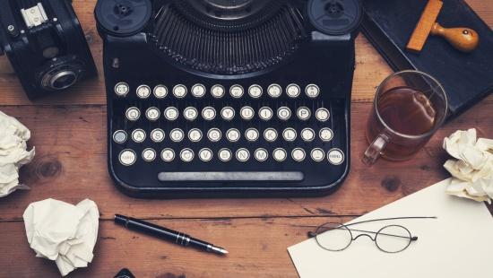 Máquina de escrever vista de cima em mesa de madeira com papeis amassados ao redor