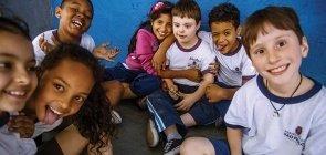 Grupo de sete alunos sentados no chão, usam uniforme da prefeitura de são paulo, sorriem para a foto