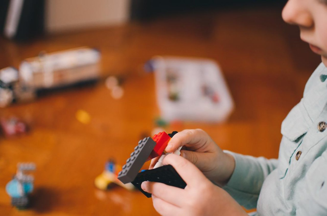 Imagem mostra mãos de criança com brinquedos pequenos e uma mesa com mais brinquedos ao fundo
