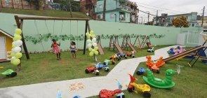 Crianças brincando no pátio de uma creche cheio de brinquedos em São Paulo