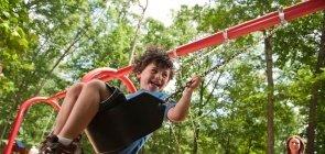 Menino brinca no balanço do parque