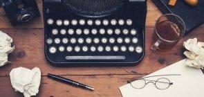 Máquina de escrever vista de cima em mesa de madeira com papeis amassados, xícara de chá, caneta e óculos espalhados