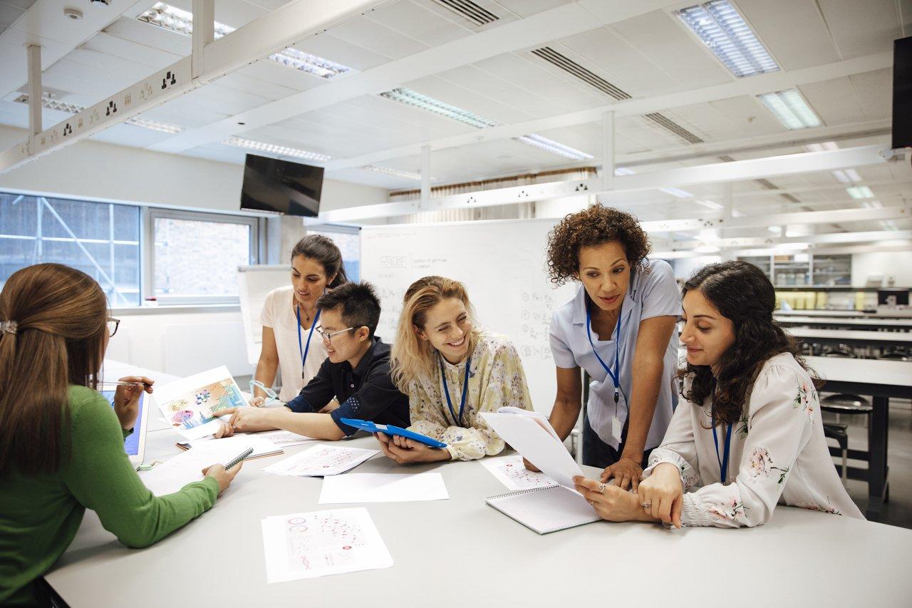 Mulheres reunidas em torno de uma mesa branca em um escritório de plano aberto, discutindo