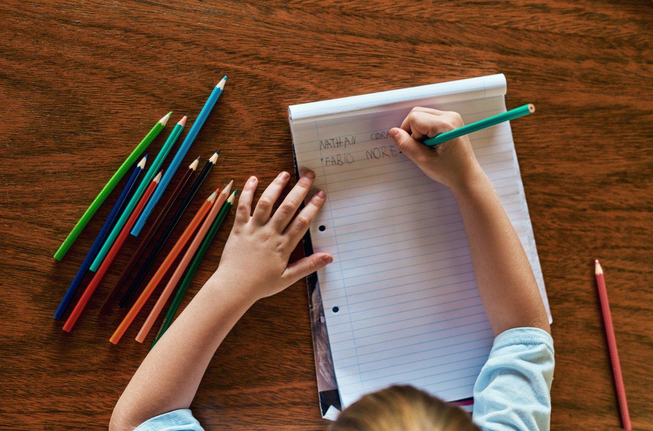 Imagem de cima de criança apoiada em mesa de madeira com caderno aberto e dois nomes escritos com lápis coloridos espalhados ao redor do caderno