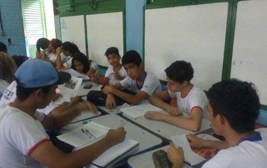 Alunos adolescentes debruçados sobre cadernos escrevendo