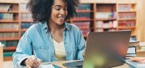Mulher anota no caderno enquanto olha para o computador