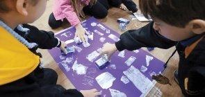 Foto de grupo de crianças pintando cartaz com moldes de figuras