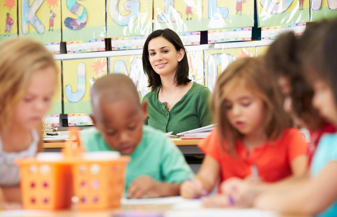 Professora sentada ao fundo de uma sala de aula observa os alunos de Educação Infantil escrevendo juntos em uma mesa em primeiro plano