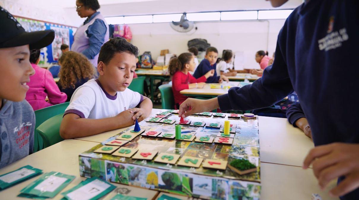 Alunos do 3º ano da EMEF Desembargador Teodomiro Toledo Piza, em São Paulo, brincam com o jogo de tabuleiro Trilha dos Seres Vivos em uma sala de aula divididos em grupos de quatro