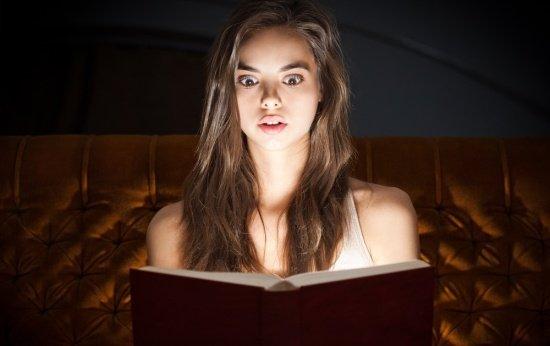 Menina se espantando lendo um livro