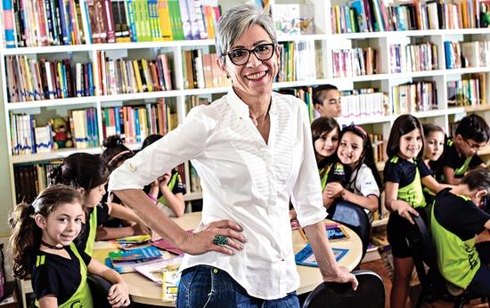 Retrato da professora Selene Coletti. Ao fundo, vê-se uma sala de aula de crianças de cerca de 7 anos.