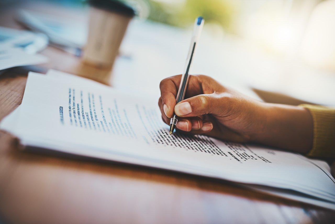 Foto mostra mão de pessoa respondendo questionário em uma mesa de madeira com um copo de café ao fundo