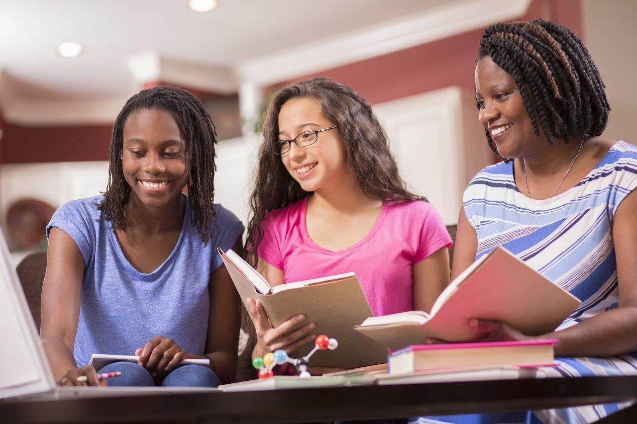 Professora e duas alunas sentadas em uma mesa baixa em meio a livros e modelos de átomos olham para tela de um computador, sorrindo