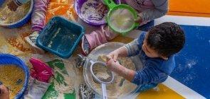 Crianças brincam com amido de milho para fazer massinha