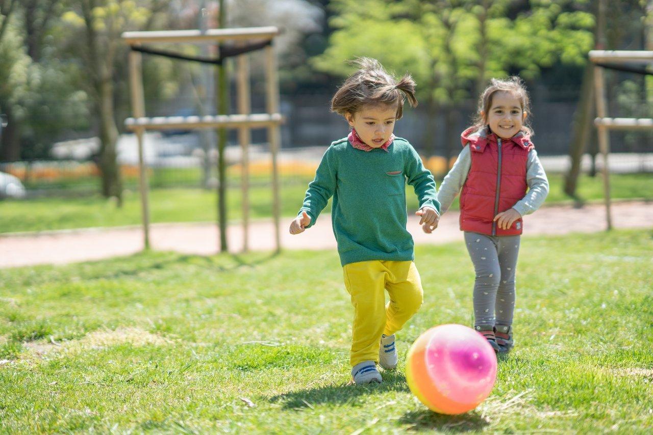Duas meninas chutam bola colorida em um gramado de um parque