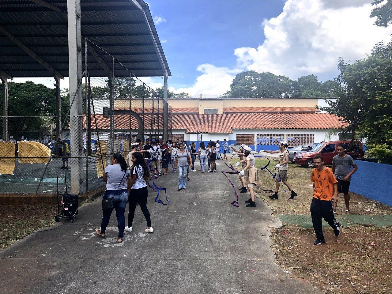 Pátio da escola Raul Brasil com atividade recreativa com palhaços e alunos brincando enfileirados