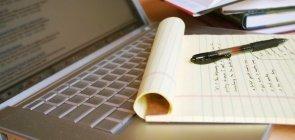 Laptop com livros, caneta e bloco de notas com anotações