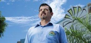 Foto de homem olhando para o horizonte, ele é branco, veste camisa azul, tem cabelo curto
