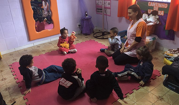 Crianças sentadas em círculo conversam durante atividade em uma creche de São Paulo